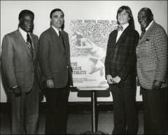 Thumbnail of Jesse Owens and three men stand around a poster of a program, 1970s
