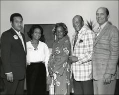 Thumbnail of Ruth and Jesse Owens pose for a photo with a group at an event, 1970s