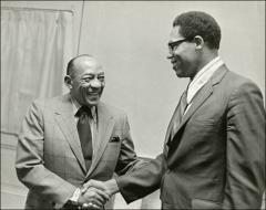 Thumbnail of Jesse Owens shakes hands with another man, 1970s