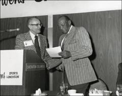 Thumbnail of Jesse Owens receives a certificate at a sports luncheon, 1970s