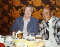 Thumbnail of Jesse Owens poses with a man at a meal, 1980