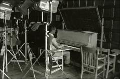 "Thumbnail of Jesse Owens plays the piano during the filming of ""The Jesse Owens Story"", 1984"