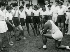 Thumbnail of Jesse Owens speaks to a group of young adults, circa 1950s