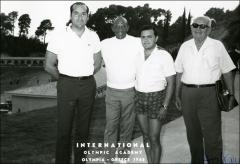 Thumbnail of Jesse Owens poses for a group photo with three other men outside the International Olympic Academy, 1969