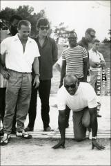 Thumbnail of Jesse Owens crouches in a start position for a group photo in Greece, 1969