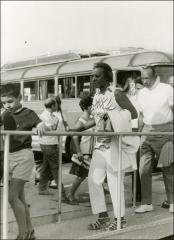 Thumbnail of Jesse Owens walks off a tour bus with Ruth Owens in Greece, 1969