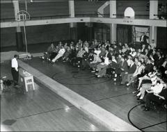 Thumbnail of Jesse Owens speaks to a group of young men in a high school, circa 1950s