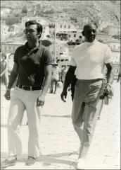Thumbnail of Jesse Owens takes a stroll with a man in Greece, 1969