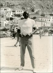 Thumbnail of Jesse Owens takes a pose along the harbor in Greece, 1969