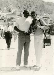 Thumbnail of Jesse Owens prepares to take a photo with a cameraman in Greece, 1969