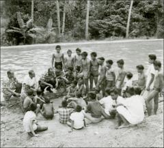 Thumbnail of Jesse Owens speaks to a group of young boys, Philippines, circa 1950s