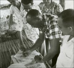 Thumbnail of Jesse Owens looks over papers, Philippines, circa 1950s